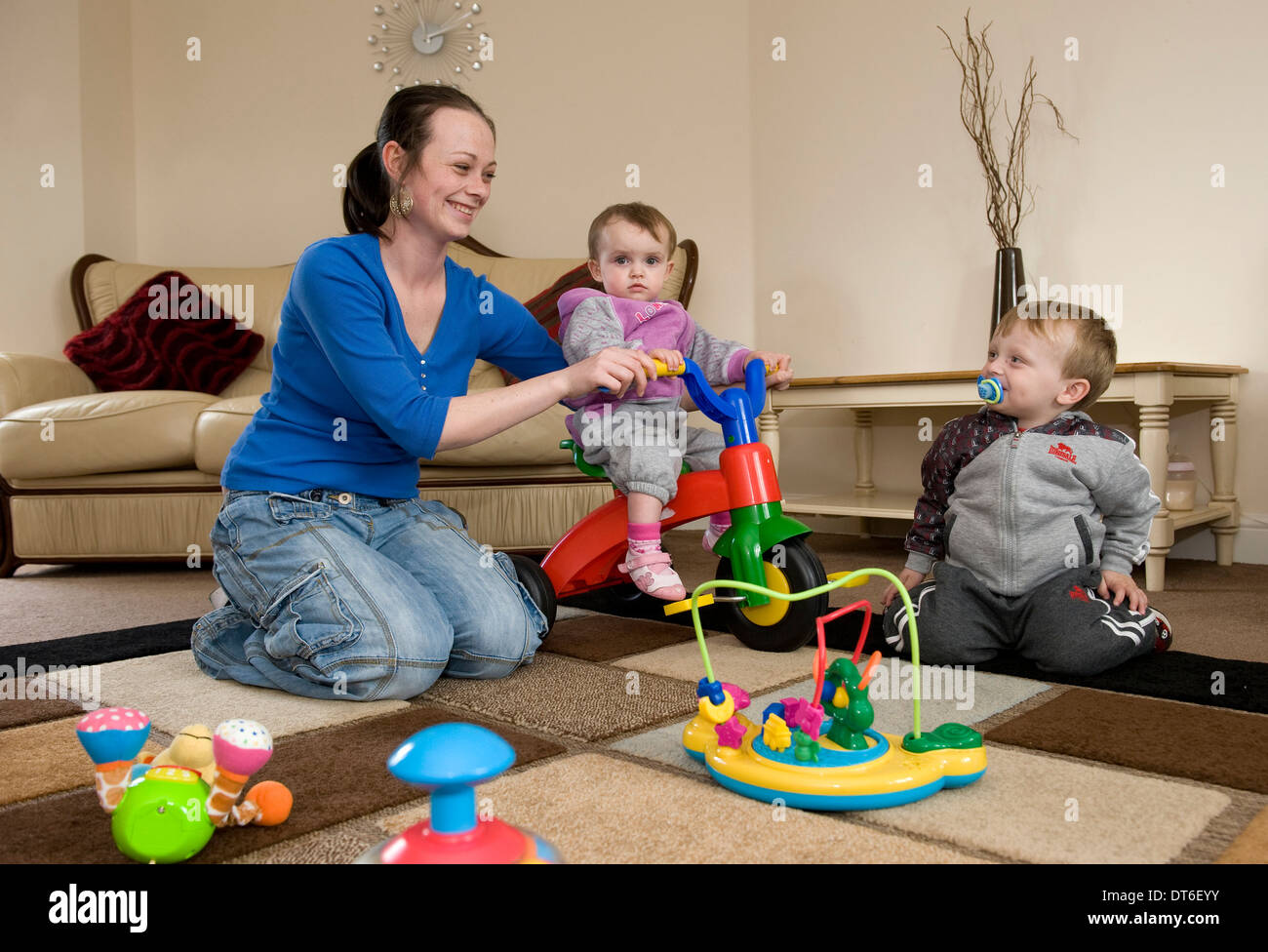 A young mother playing with her two children at their home. - Stock Image