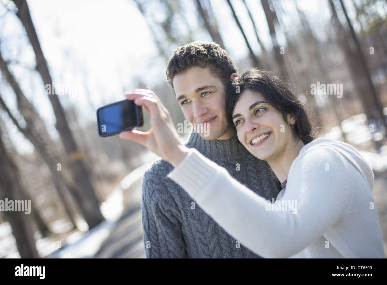 A couple outdoors on a snowy day. Woman holding a camera phone, taking photographs at arms length. - Stock Image
