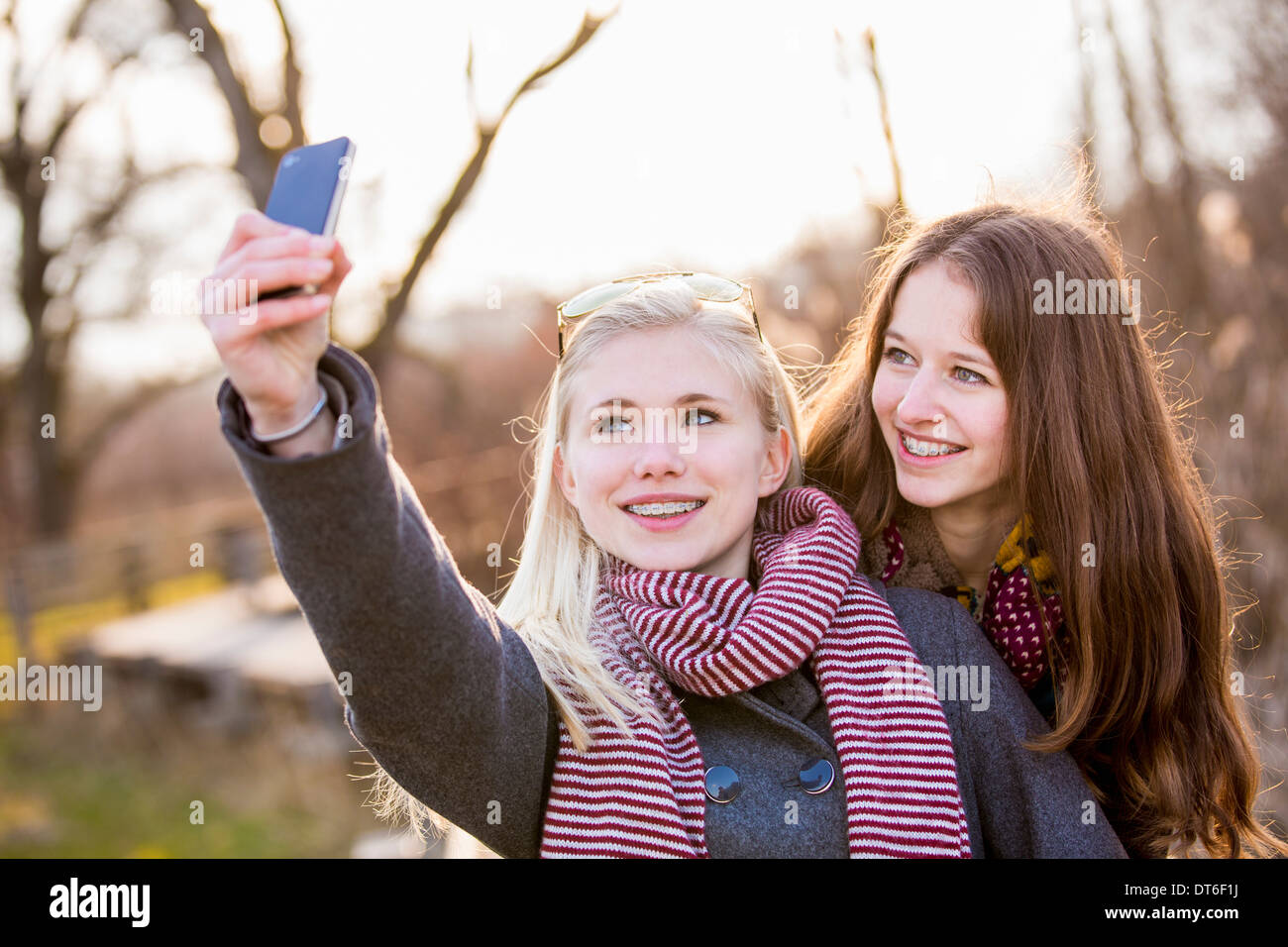 Teenage girls photographing themselves with smartphone Stock Photo