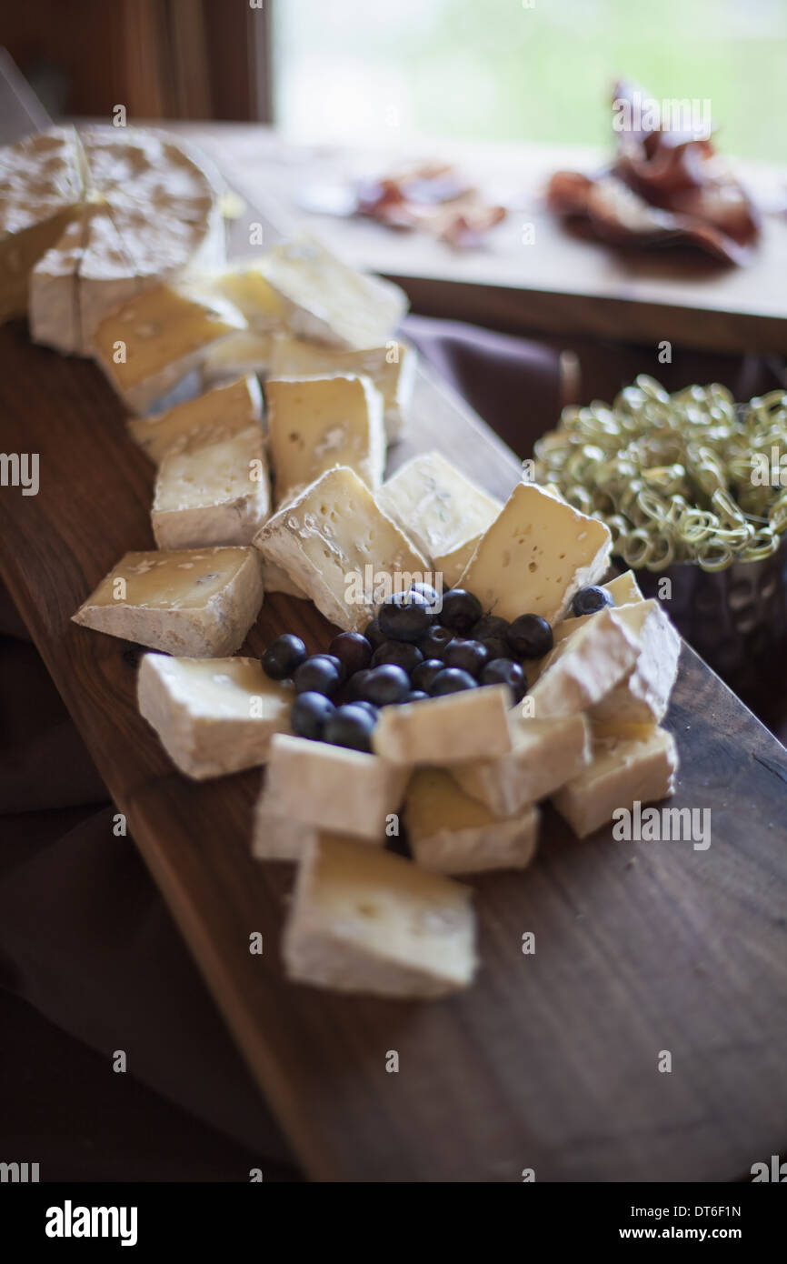A wedding party meal.  A cheeseboard, with soft cheeses cut into triangles, and fresh fruits. Blueberries. - Stock Image