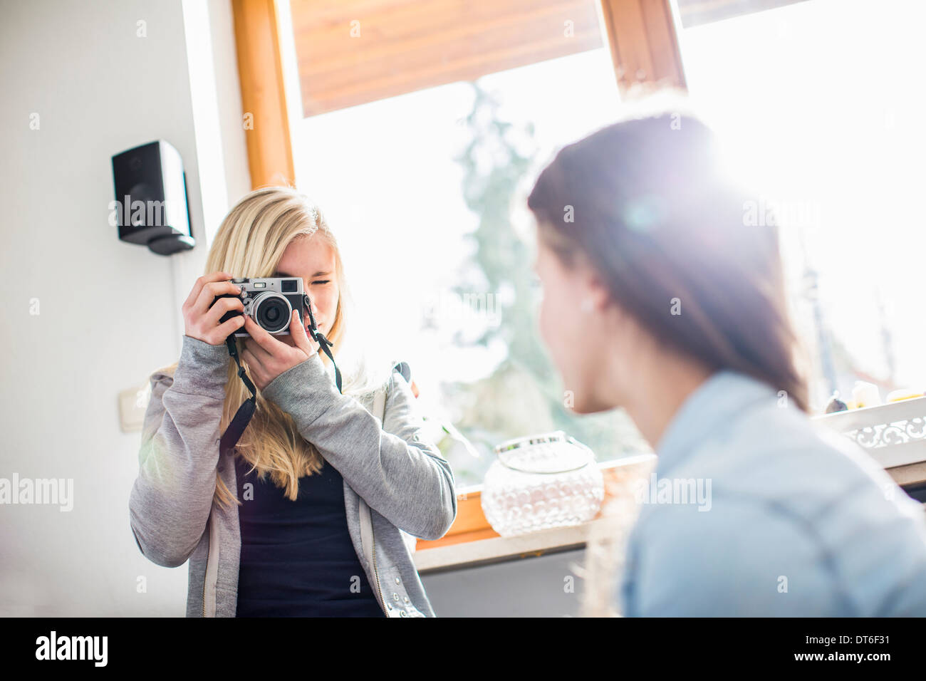 Teenage girl photographing friend with camera - Stock Image