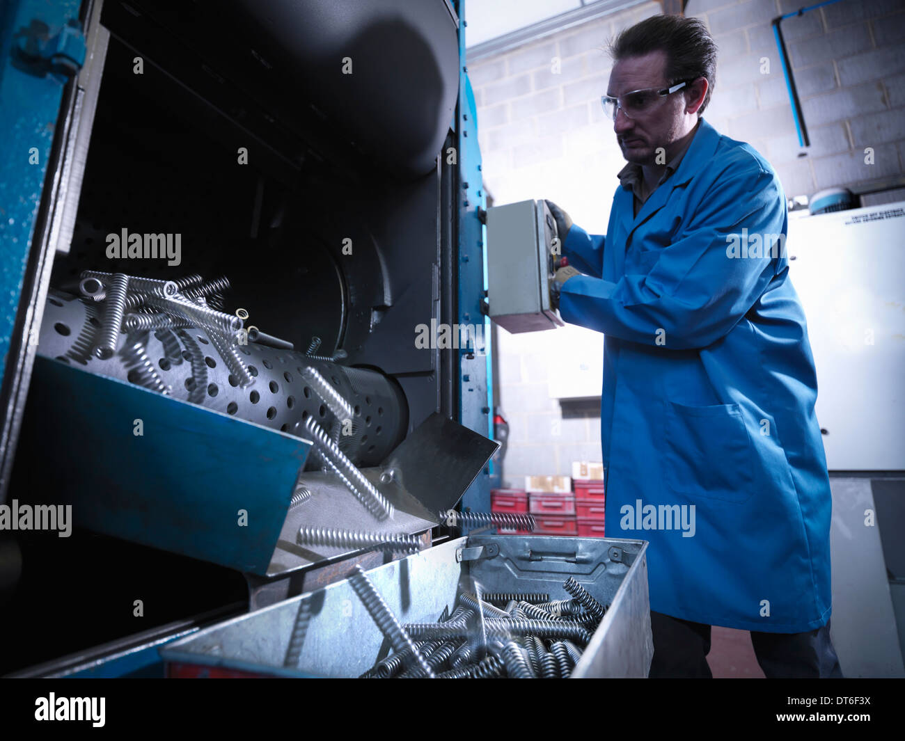 Worker shot blasting springs in laboratory - Stock Image