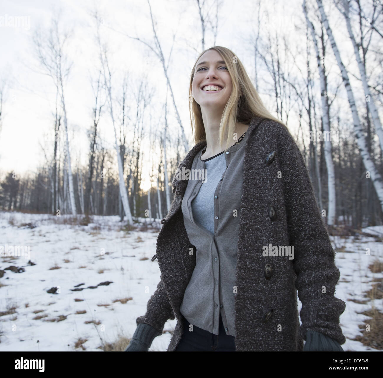 A young woman with long blonde hair outdoors on a winter day. - Stock Image