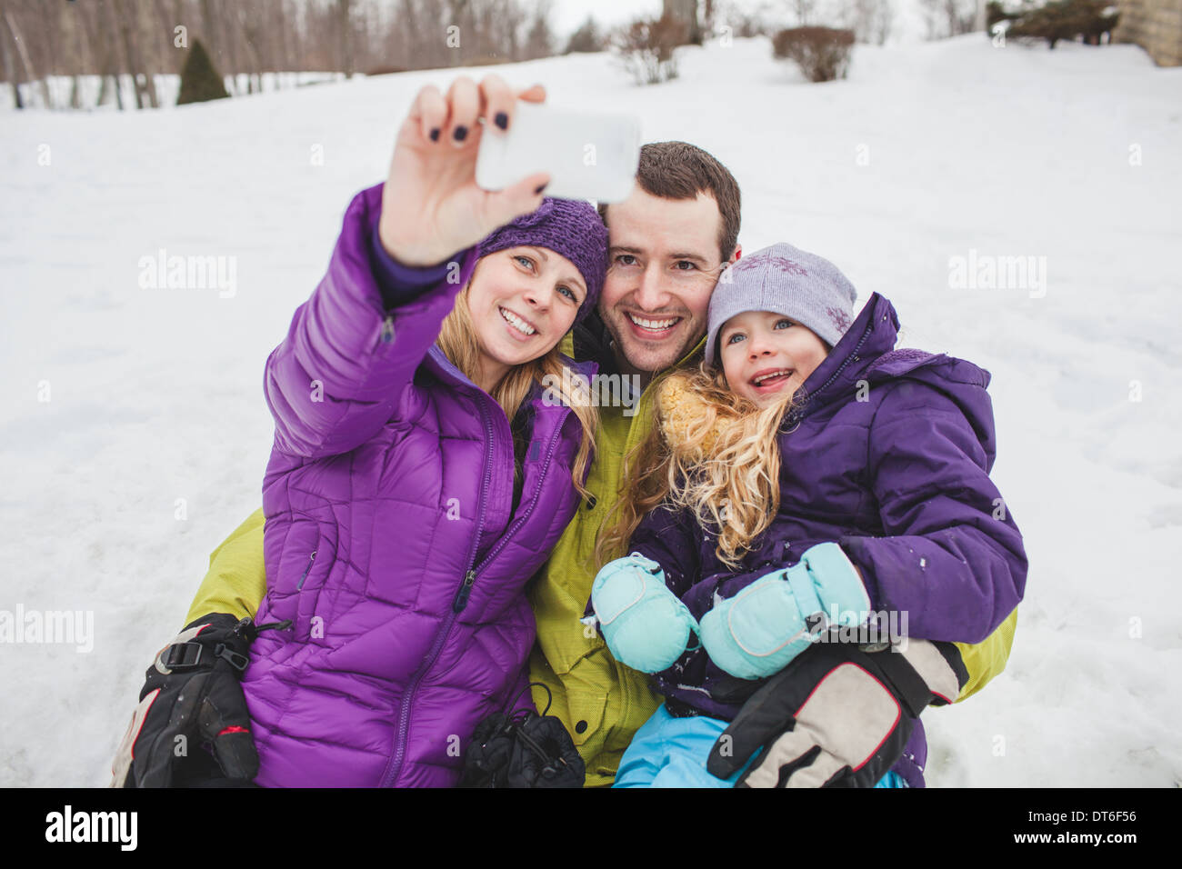 Mother and Father with daughter taking family portrait with mobile phone - Stock Image