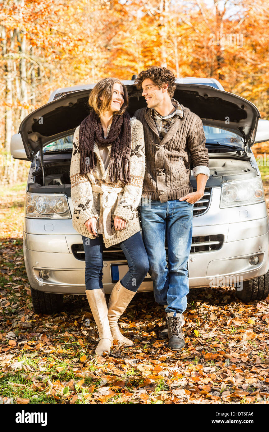 Couple leaning against car that has broken down - Stock Image
