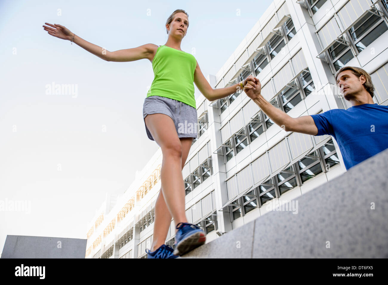 Young woman walking on wall holding man's hand - Stock Image