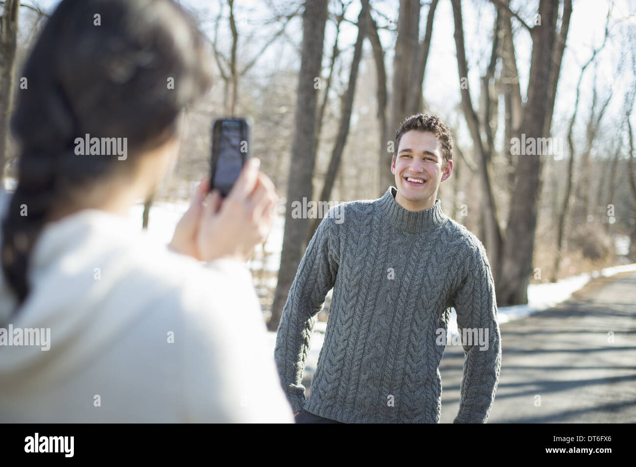 A couple outdoors on a snowy day. A woman holding a camera phone, taking photographs of a man. - Stock Image
