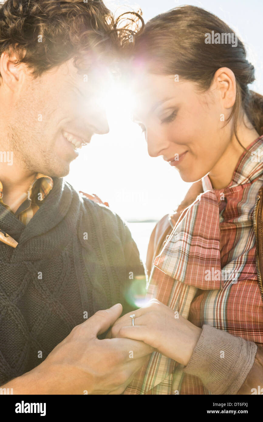 Man holding woman's hand, woman wearing engagement ring Stock Photo