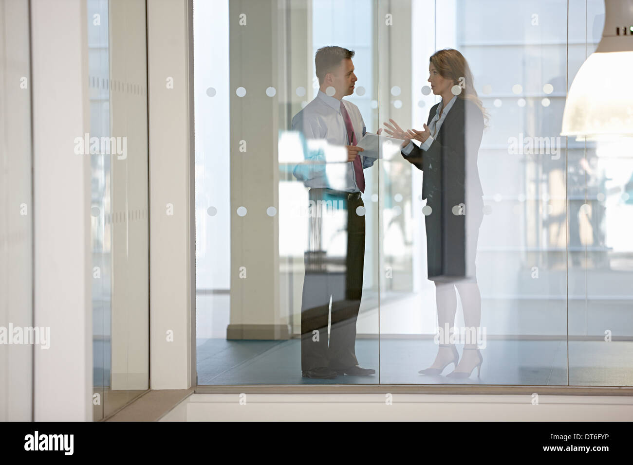 Business colleagues in discussion through glass - Stock Image