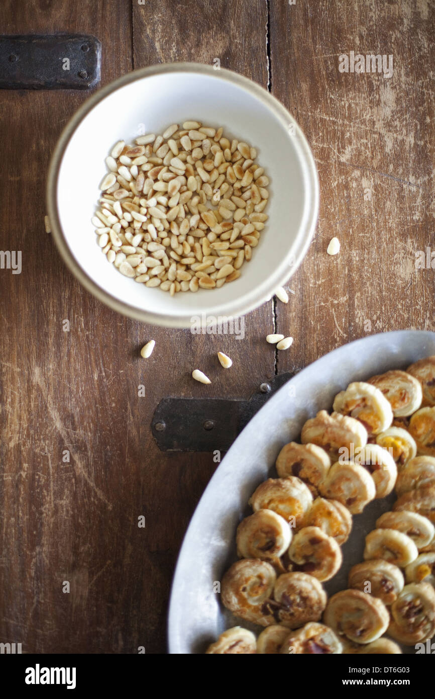 A white pottery bowl, full of dried corn kernels. A dish of baked pastries. - Stock Image