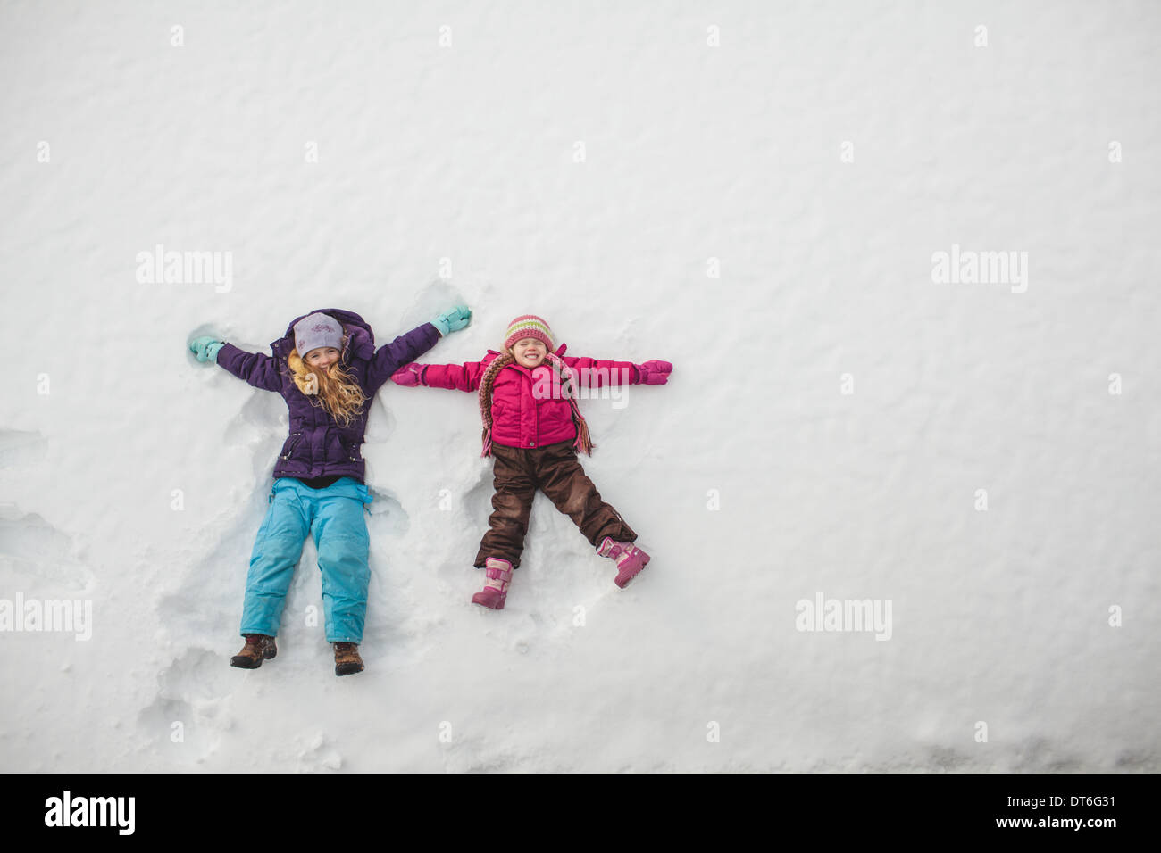 Two sisters playing, making snow angels in snow - Stock Image