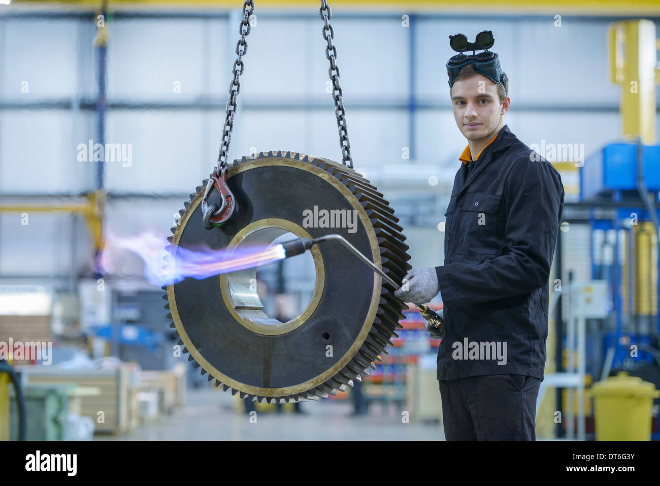 Portrait of engineer heat treating industrial gear in factory - Stock Image