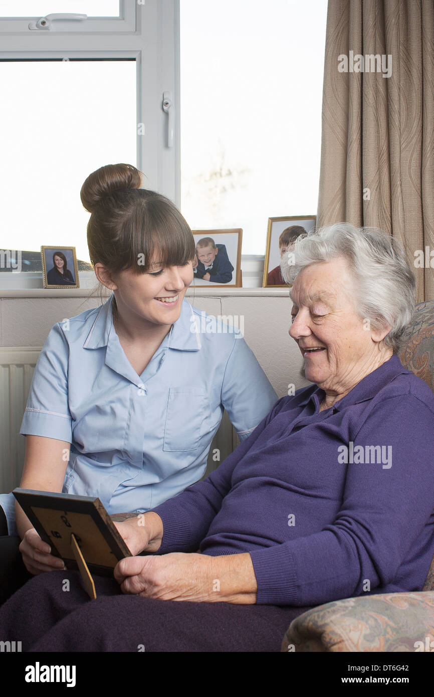 Personal care assistant looking at photograph with senior woman - Stock Image