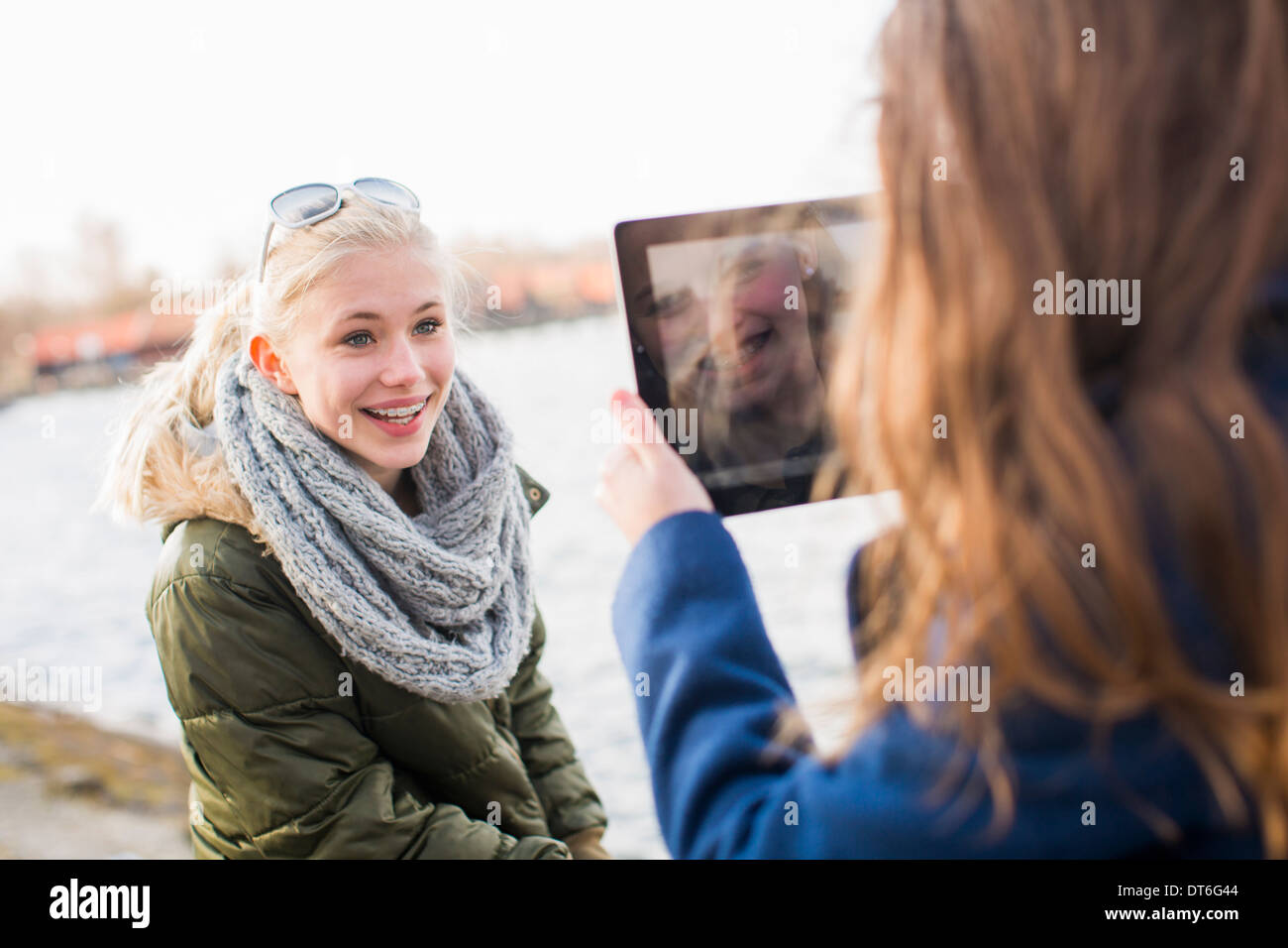 Teenage girl photographing friend with digital tablet - Stock Image