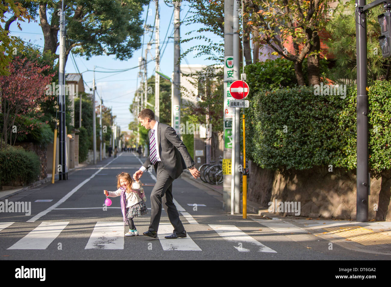 Father and daughter crossing zebra crossing Stock Photo
