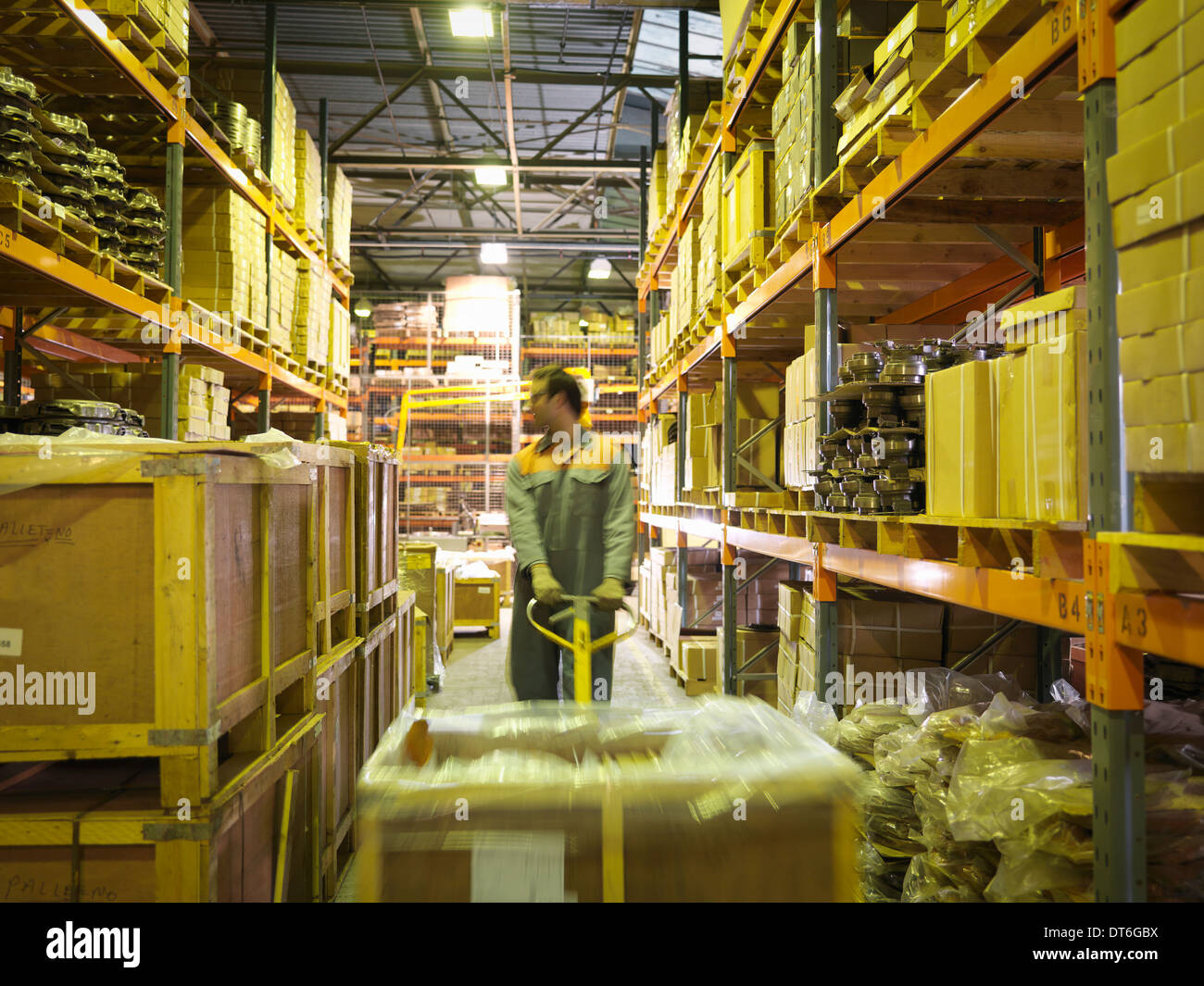 Worker in storage area of factory - Stock Image