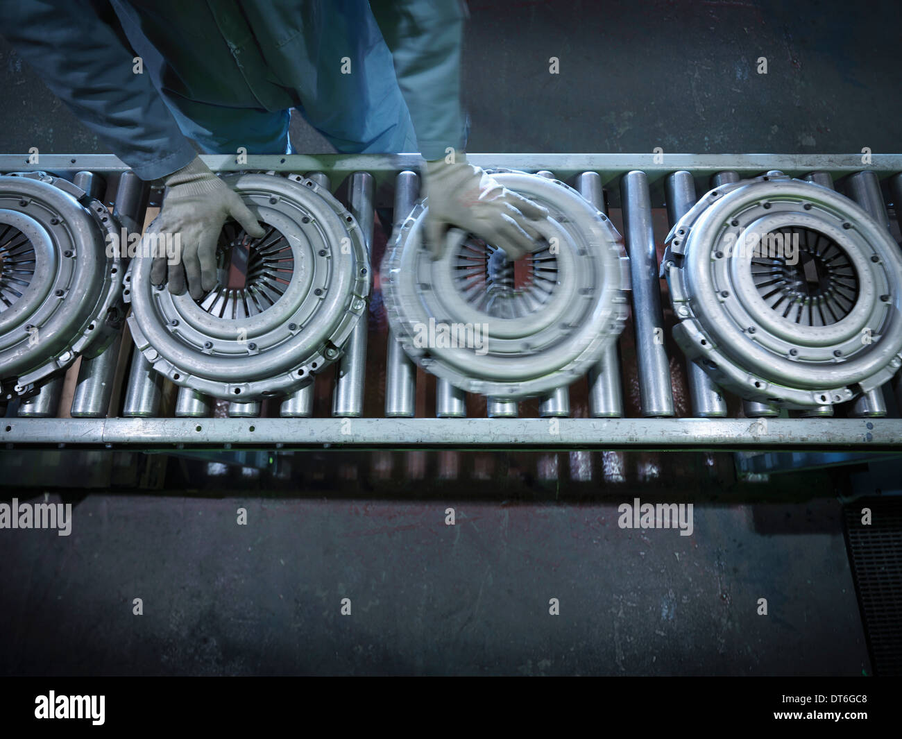 Overhead view of worker on production line in industrial clutch factory - Stock Image