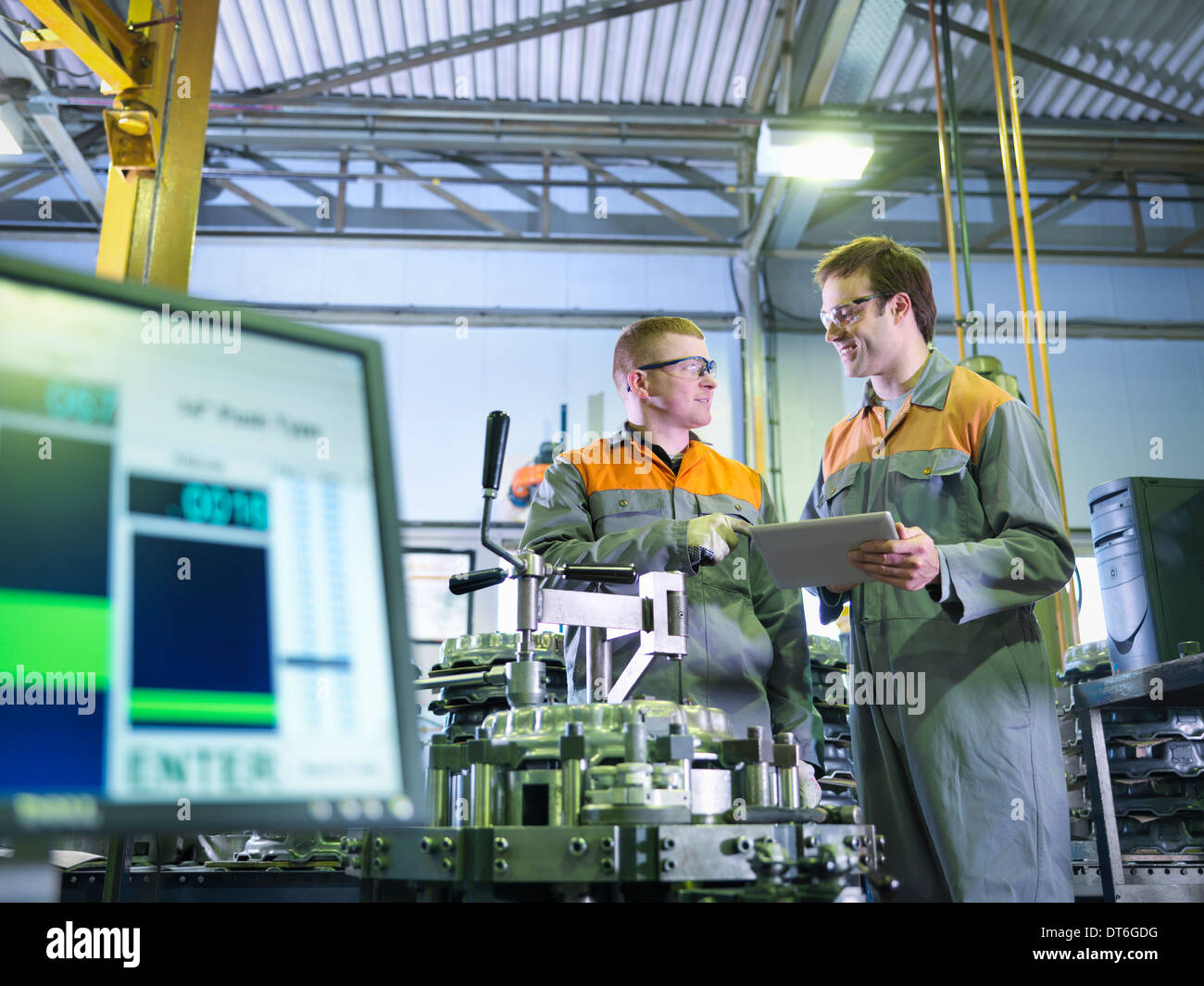 Engineer and apprentice using digital tablet at work station in factory - Stock Image
