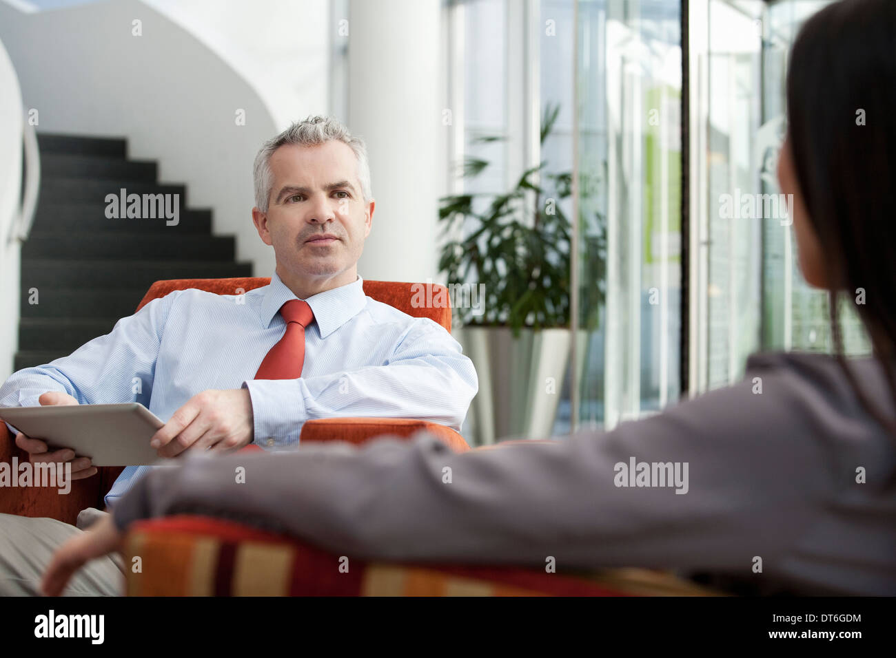 Businessman holding interview in office - Stock Image