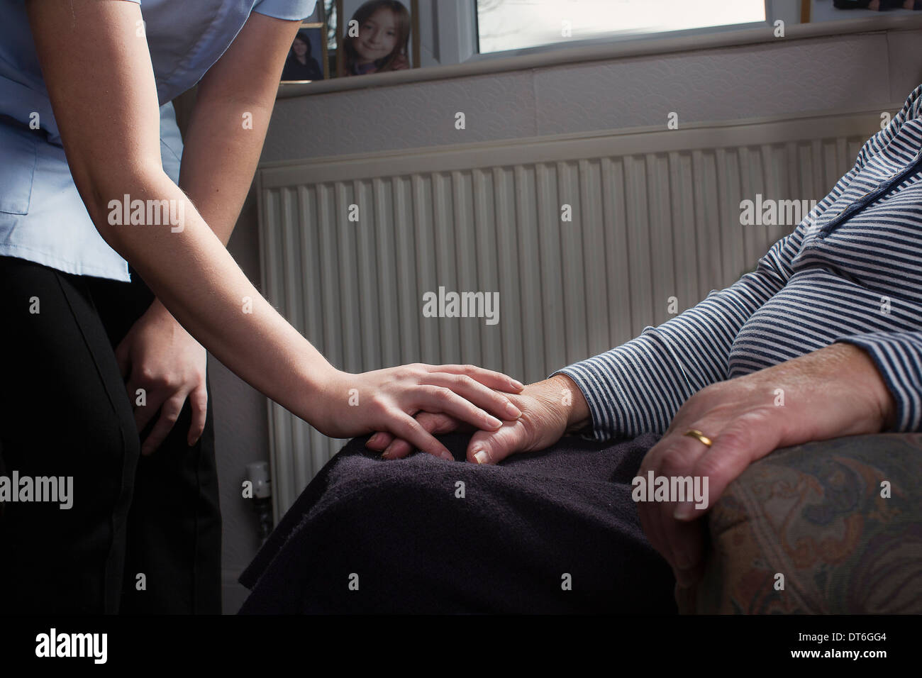 Personal care assistant comforting senior woman - Stock Image