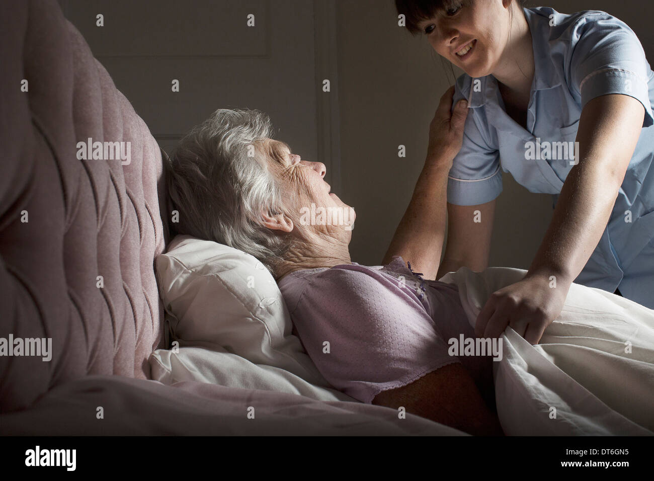 Personal care assistant chatting to senior woman in bed - Stock Image