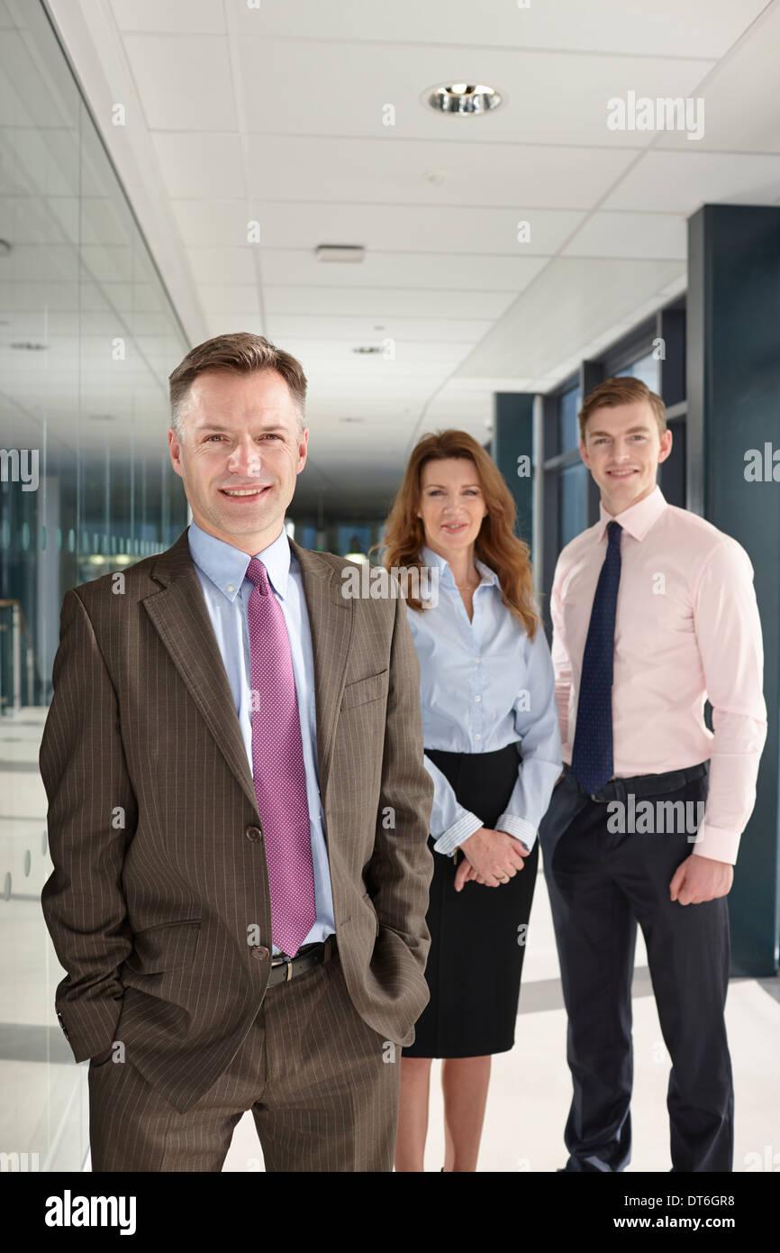 Portrait of business colleagues in corridor - Stock Image