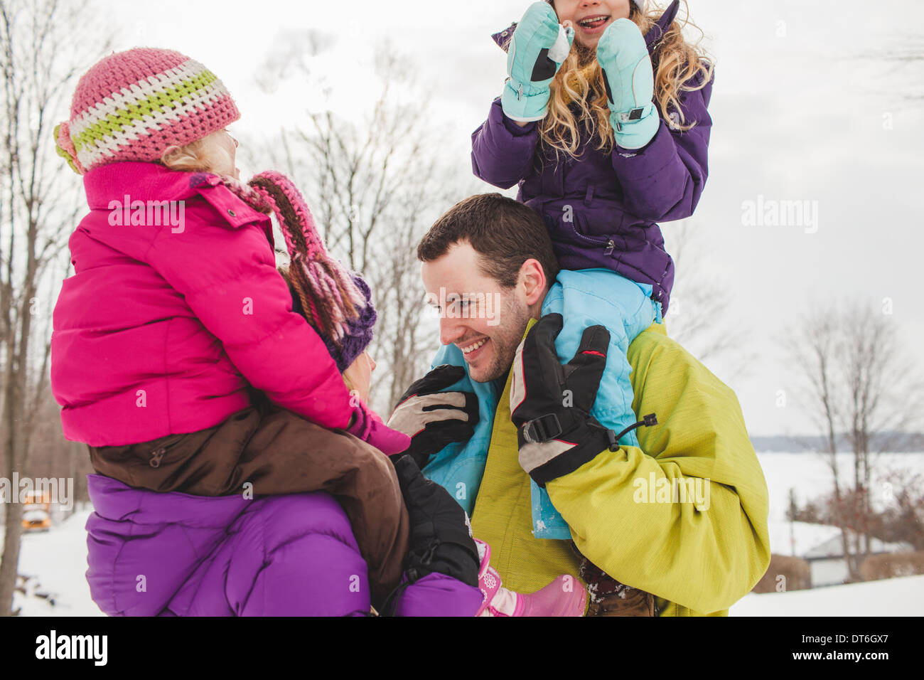 Mother and father carrying daughters in snow Stock Photo