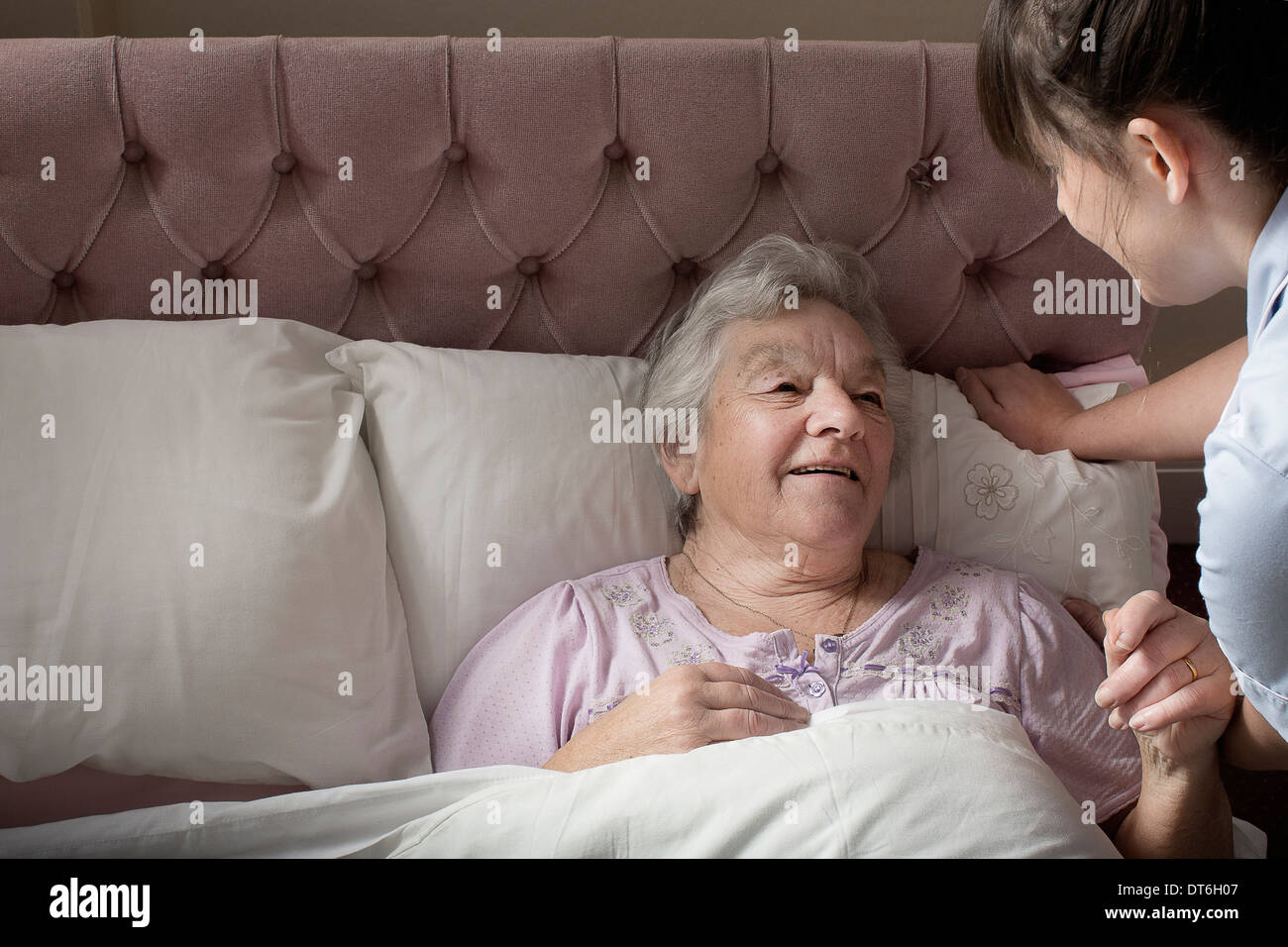 Personal care assistant chatting to senior woman in bed Stock Photo