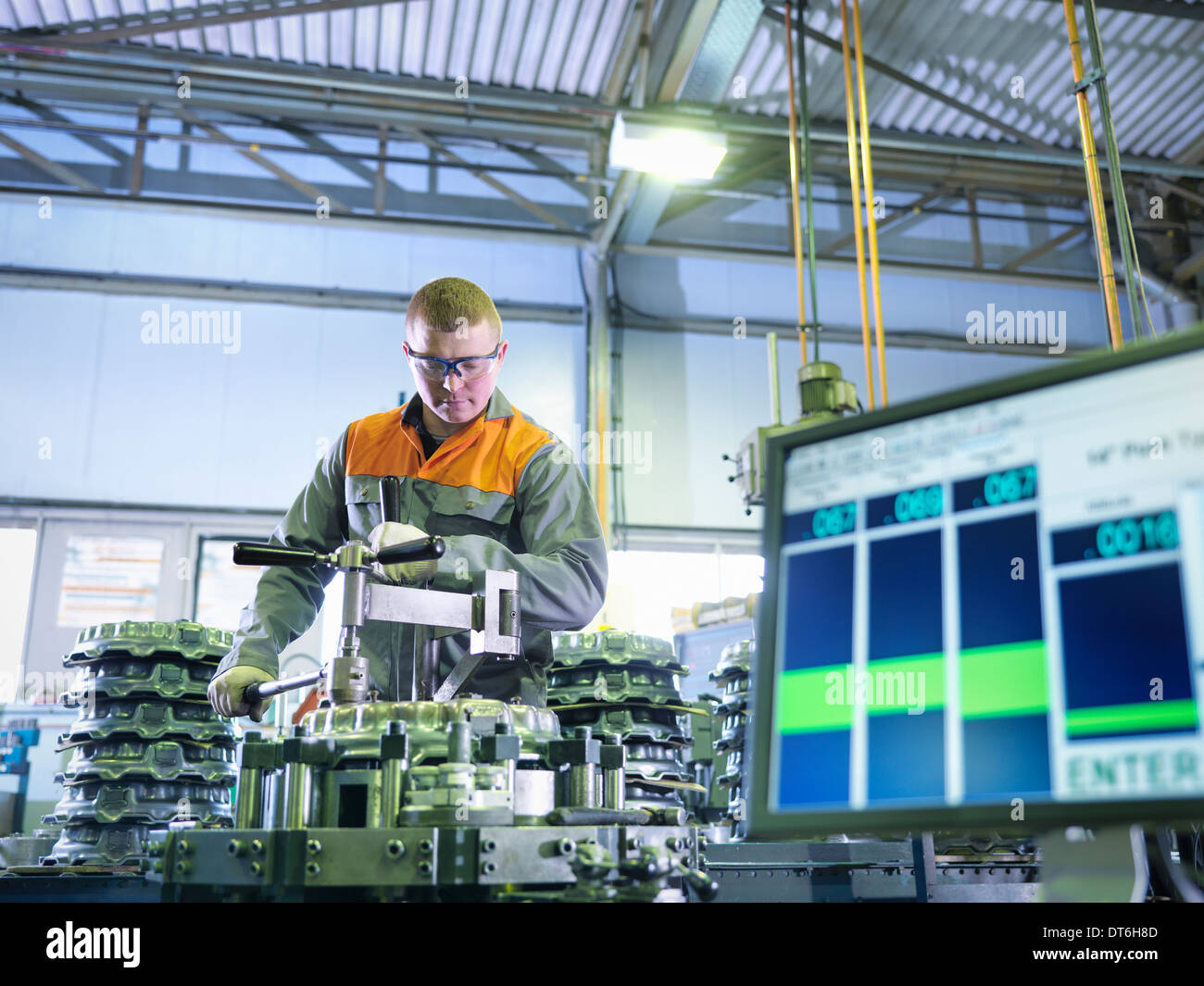 Worker assembling and testing clutches on rig in factory - Stock Image