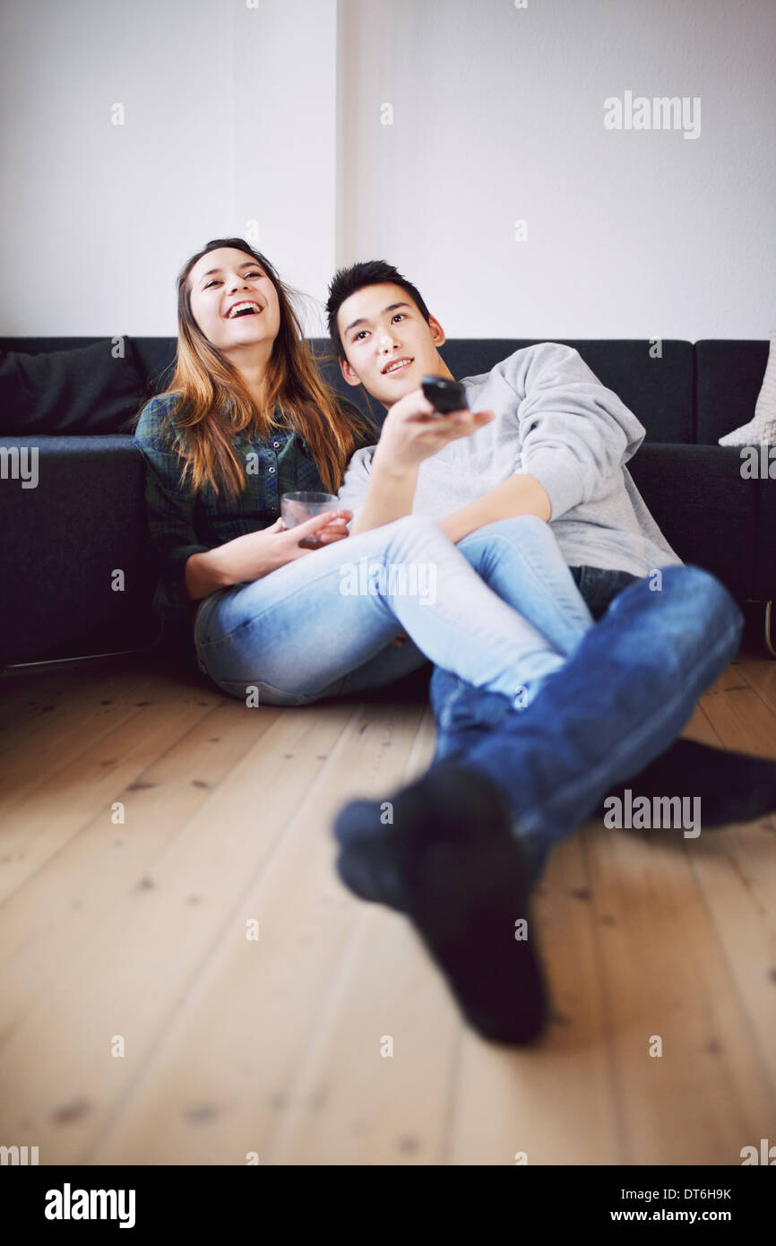 Handsome young man holding remote control changing channels sitting with his beautiful girlfriend laughing while watching TV. - Stock Image