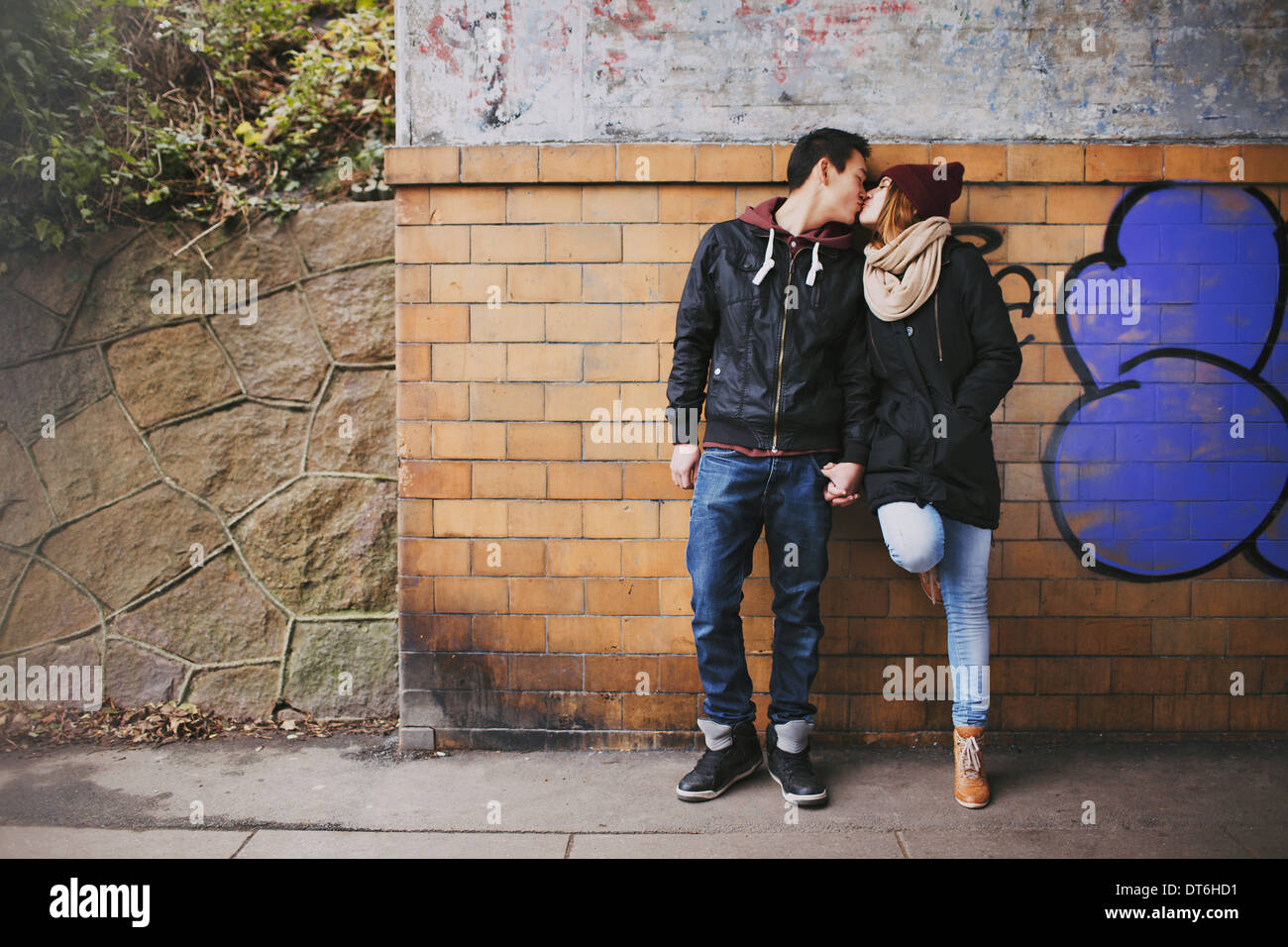 Affectionate teenage couple kissing outdoors against a wall on street. Mixed race couple in love. - Stock Image