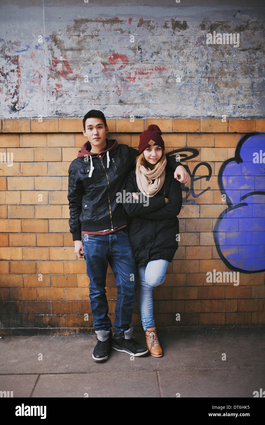 Full length portrait of handsome young man standing with his beautiful girlfriend leaning against a wall. - Stock Image