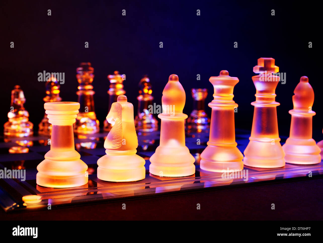 Glass chess on a chessboard lit by a colorful blue and orange light and placed on a glass chessboard - Stock Image