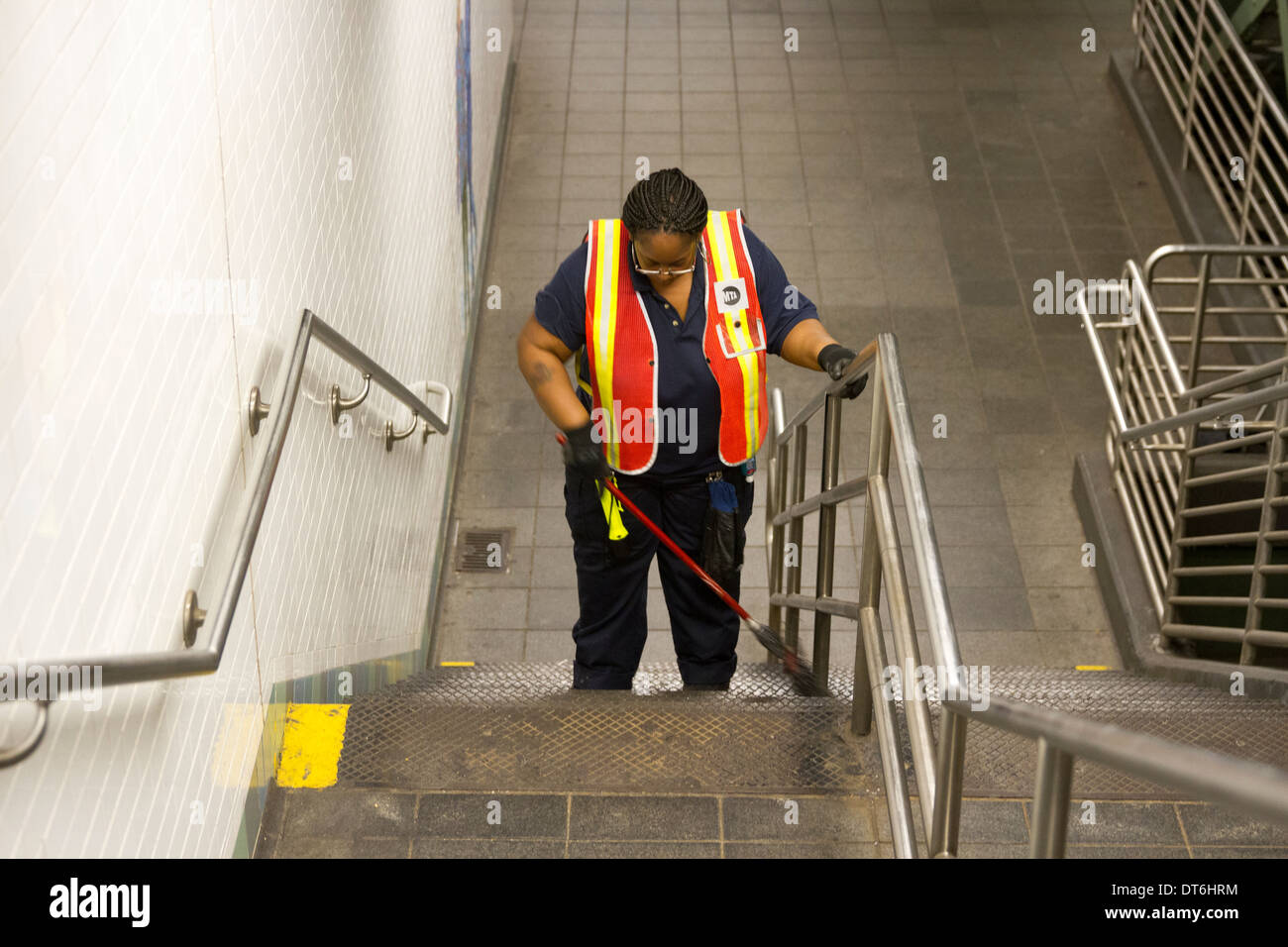 Women Cleaning inside the train station - Stock Image