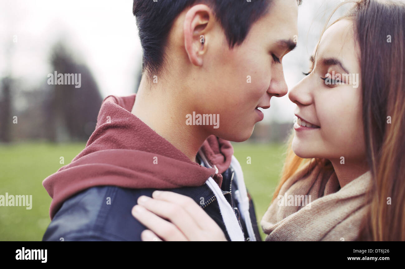 Closeup image of romantic young couple in park. Asian teenage couple about to kiss each other while outdoors on a date. - Stock Image