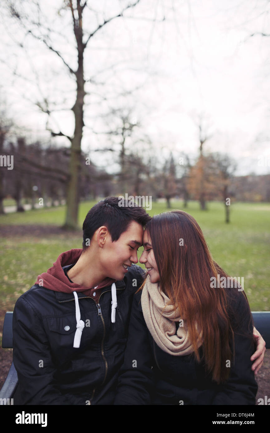 Teenage couple sitting on a bench and enjoying a day in the park. Beautiful young couple in park. Mixed race male and female. - Stock Image