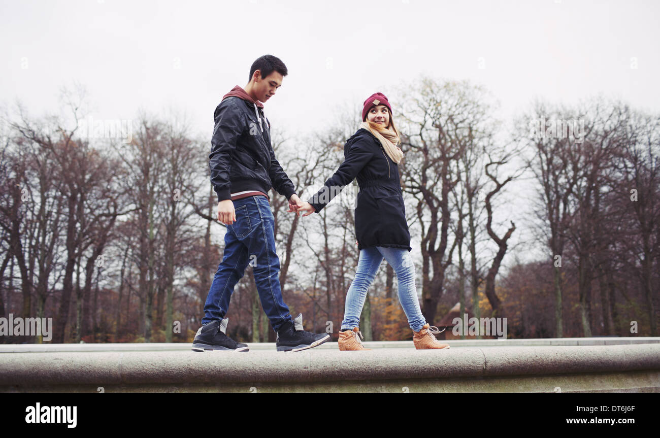 Low angle view of handsome young man with his girlfriend walking together holding hands in park. Mixed race teenage couple. - Stock Image
