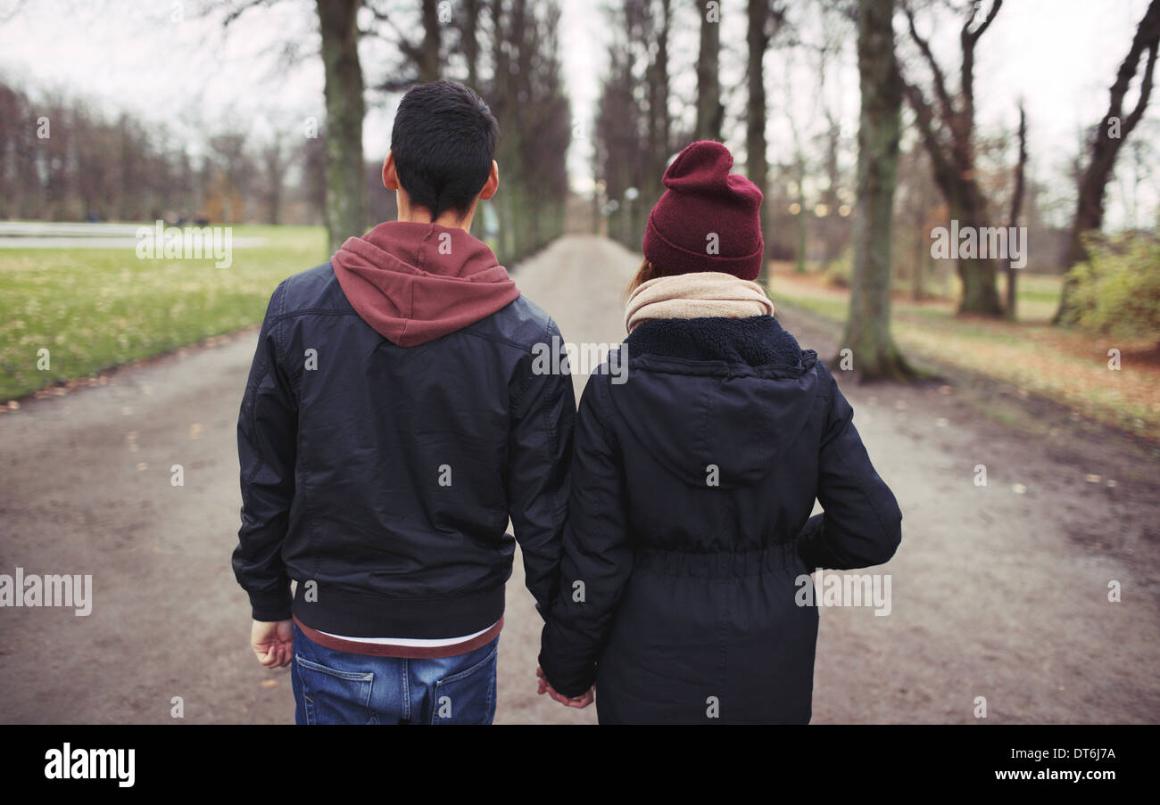Rear view of teenage couple walking in park holding hands. Young man and woman in warm clothes outdoors. Stock Photo
