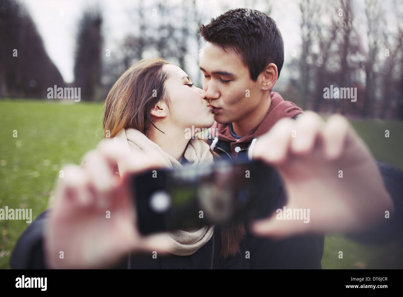 Lovely young couple taking self portrait while kissing at the park. Teenage boy and girl with smartphone outdoors. - Stock Image
