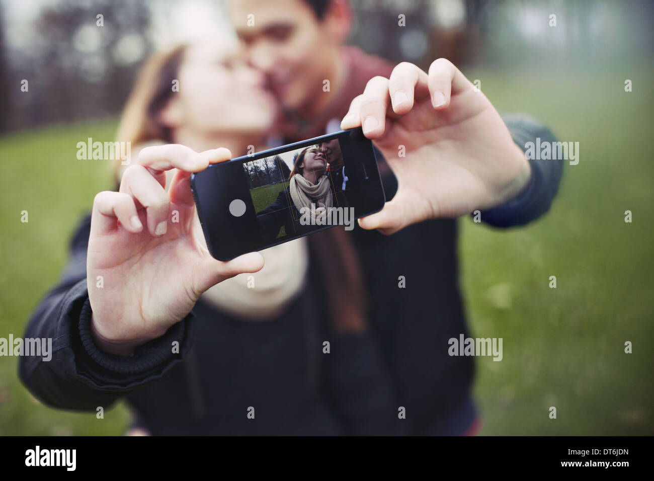 Romantic teenage couple taking self portrait with cell phone at the park. Young man and woman in love. - Stock Image