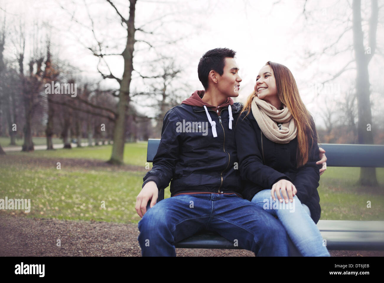 Happy young couple sitting on a bench outdoors during winter season. Asian teenage couple in warm clothes sitting on park bench. - Stock Image