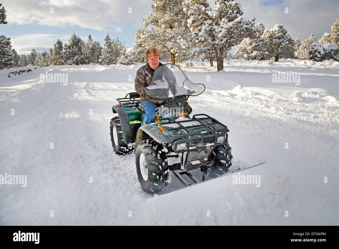 A senior citizen plows snow with an ATV, all terrain vehicle, after a major snow storm in central Oregon. - Stock Image