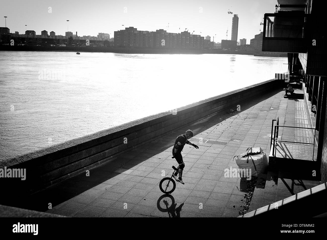 Unicyclist, Silhouetted next to the River Thames London. Stock Photo