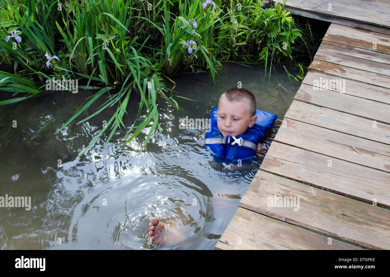 young boy in life preserver life jacket life vest swimming in pond - Stock Image