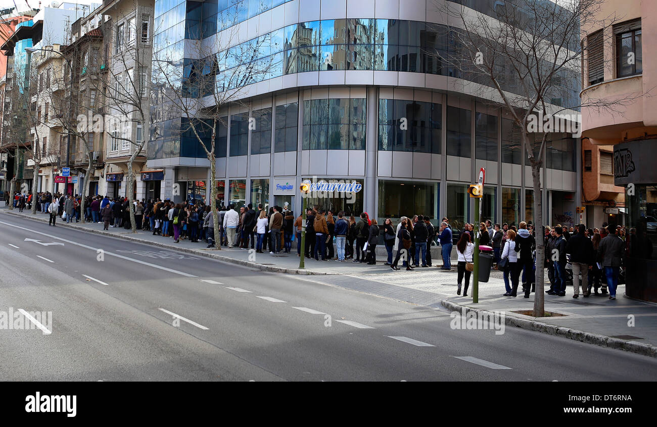 People await in queue their turn to apply for a job offer in the island of Mallorca, Spain - Stock Image