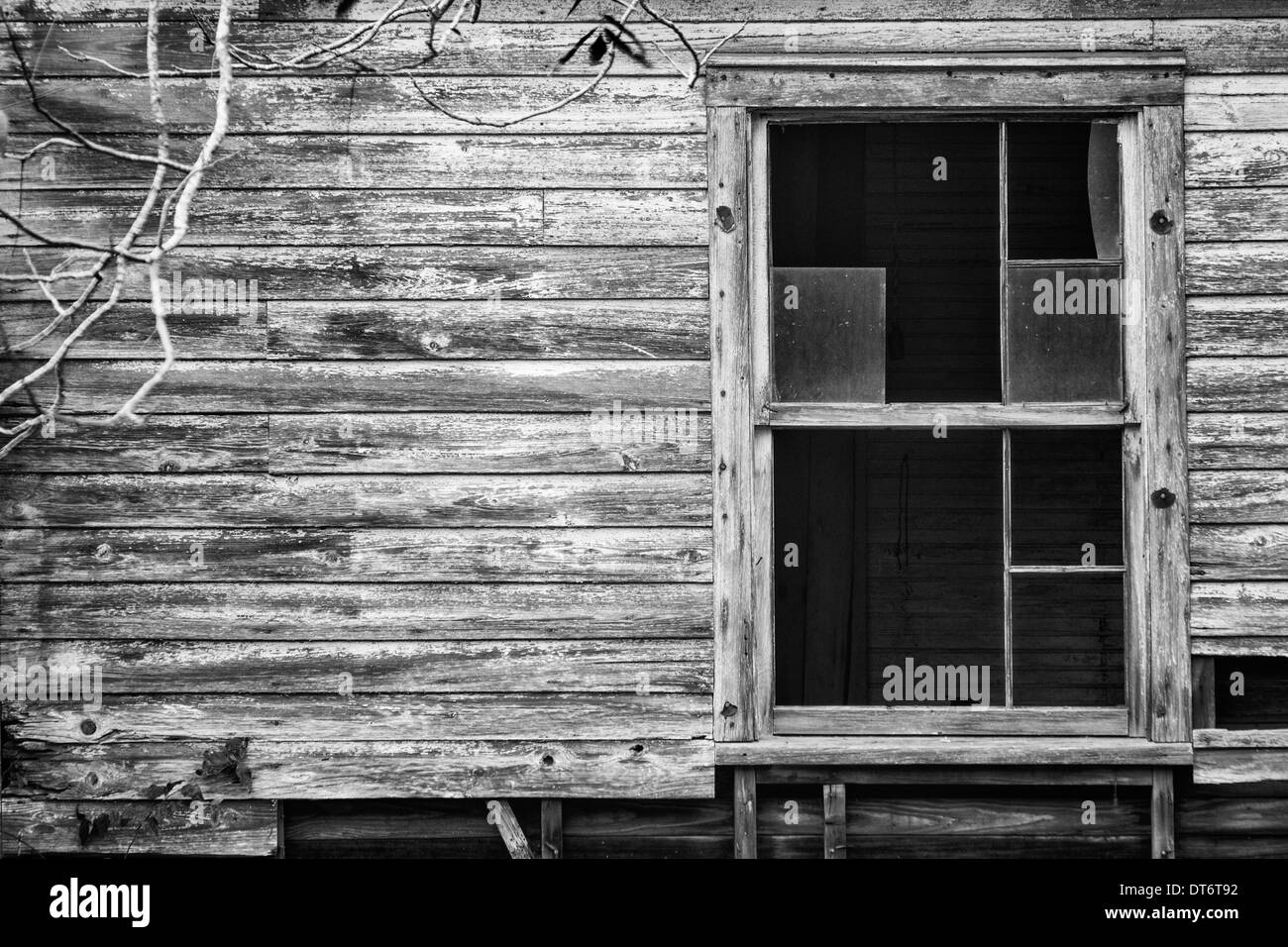Broken window in a ramshackle house in Fernandina Beach, Florida. Converted to black and white. - Stock Image