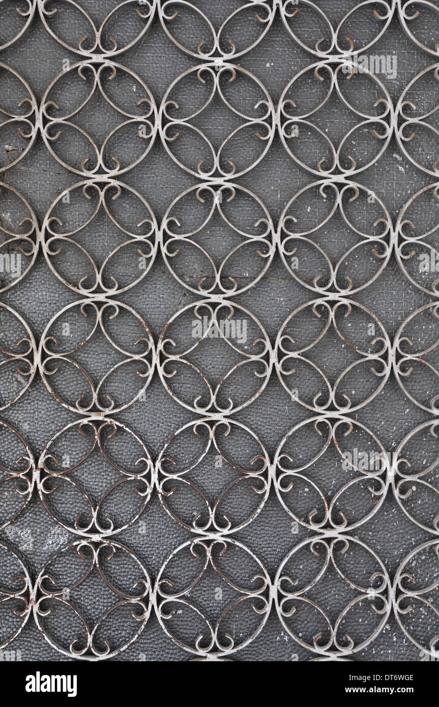 Vintage iron door frame with circles pattern detail and stained glass background. Stock Photo