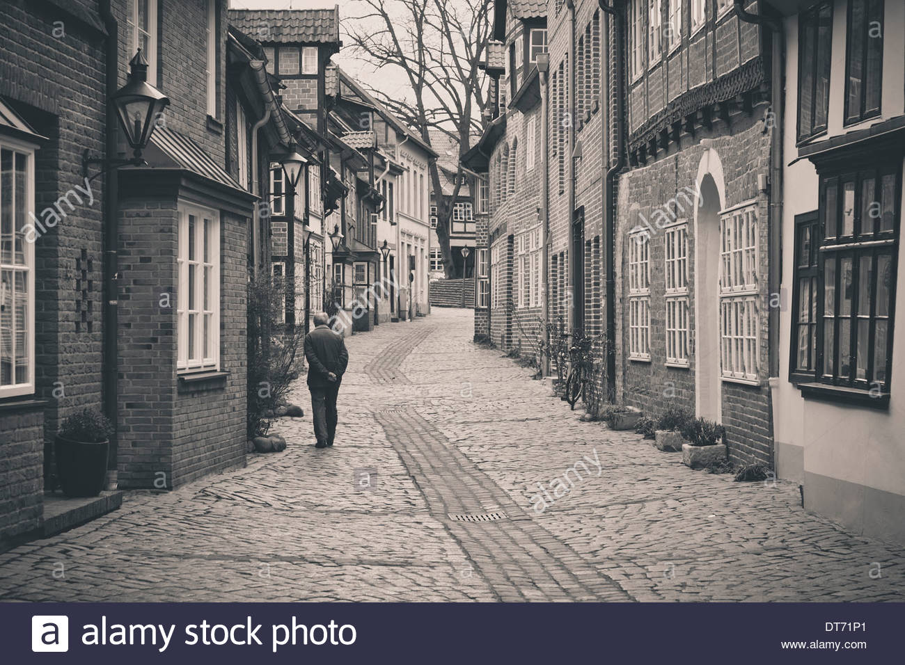 Old man walking down a cobbled street in Lüneburg old town, Lower Saxony, Germany - Stock Image