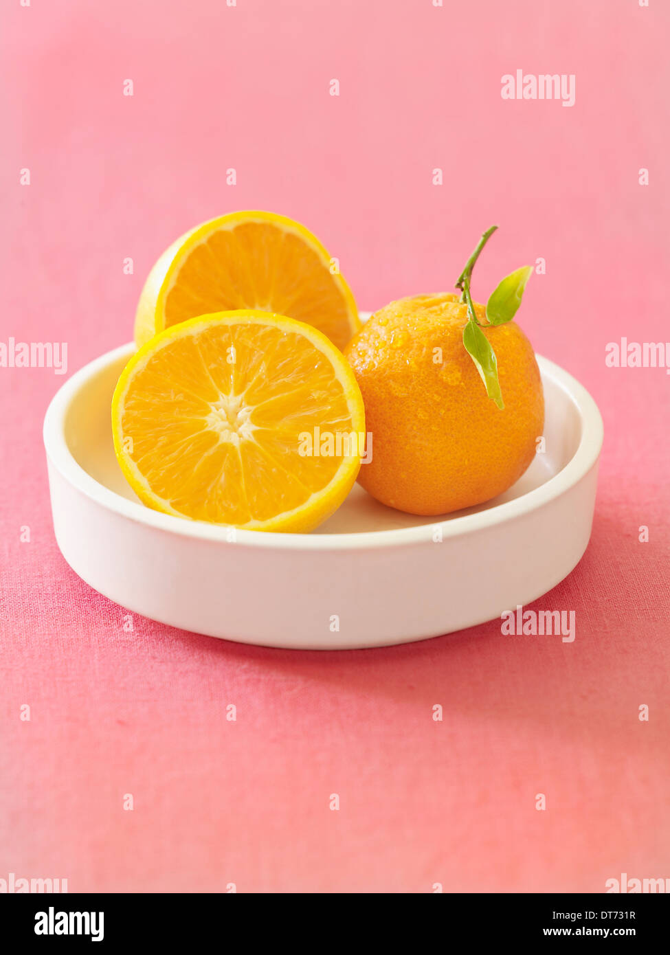 A white bowl with oranges whole and cut on a pink fabric background. - Stock Image