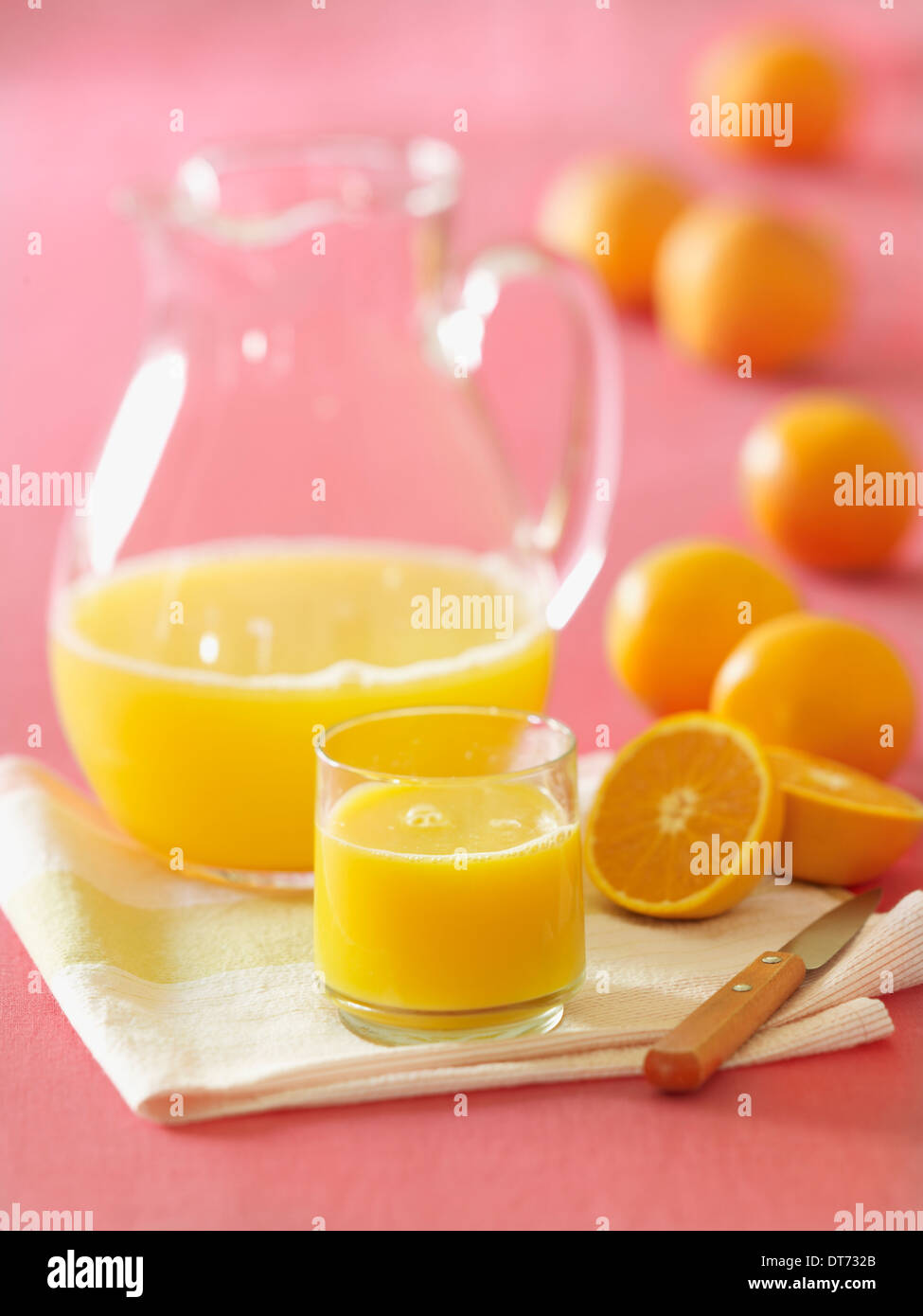 A glass pitcher of orange juice with a glass filled with fresh squeezed orange juice with several oranges in the background. - Stock Image